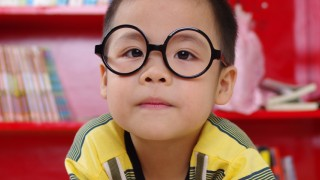 child wearing glasses reading book