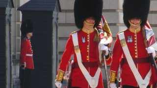 Two royal guards carrying flag in front of Buckingham Palace