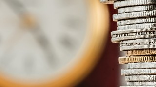 Stack of coins in front of an out of focus clock