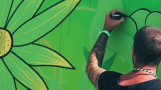 Man drawing flowers on a wall