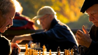 older people playing chess in park
