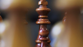 Close up of the King chess piece on a chess board